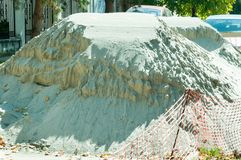 大堆在都市城市街道重建工作地点的沙子有一部分的橙色塑料安全网 库存照片
