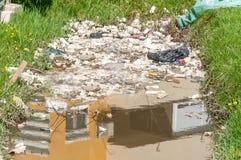 大堆垃圾和破烂物在污染自然与废弃物的河水 图库摄影