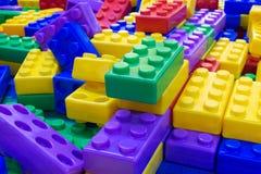 大堆塑料玩具阻拦孩子教育概念的背景 免版税库存图片