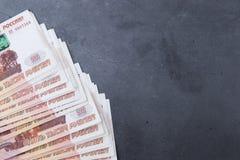 大堆说谎在灰色水泥背景的五千卢布俄国金钱钞票  免版税库存照片