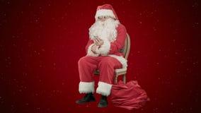 大声笑的圣诞老人,他在他的在红色背景的手机谈话与雪 免版税库存照片
