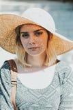 戴大夏天帽子的逗人喜爱的女孩假装是妇女夫人 免版税库存图片