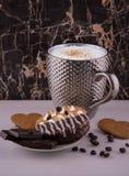 大多粉刺银色咖啡和蛋糕bisquits巧克力和白色反射性表面上的咖啡豆 库存图片