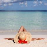 大太阳帽子的妇女从放松在热带海滩。 免版税库存照片