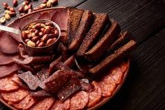 大套啤酒的快餐或酒精和它包括坚果、saucage、蒜味咸腊肠和黑麦面包 图库摄影