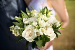 大好的婚礼花束在妇女` s手上 新娘和新郎在他们婚礼拥抱 免版税库存图片