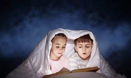 大字书写的女孩和男孩看书 库存照片