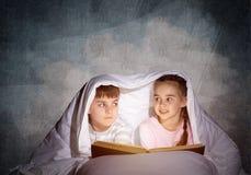 大字书写的女孩和男孩看书 库存图片