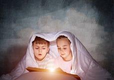 大字书写的女孩和男孩看书 免版税库存图片