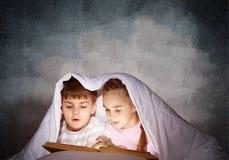 大字书写的女孩和男孩看书 免版税库存照片