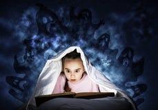 大字书写的女孩看书在床上 免版税库存图片