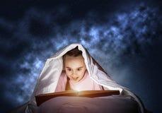 大字书写的女孩看书在床上 库存照片
