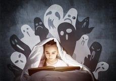 大字书写的女孩看书在床上 库存图片