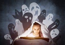 大字书写的女孩看书在床上 免版税库存照片