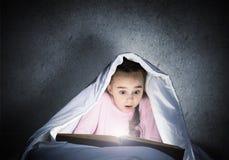 大字书写的女孩看书在床上 免版税图库摄影
