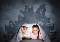 大字书写的小孩看书在床上 免版税库存照片