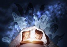 大字书写的小孩看书在床上 免版税图库摄影