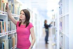 大学图书馆俏丽的学员年轻人 免版税库存图片