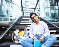 大学大厦的年轻逗人喜爱的印地安女孩坐台阶 免版税库存图片