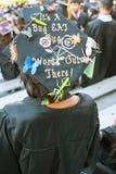 大学毕业生佩带与滑稽的消息的灰浆板 图库摄影