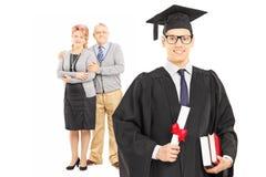 大学毕业生和他骄傲的父母 免版税库存照片