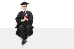 大学毕业生坐一个空白的广告牌 免版税库存图片