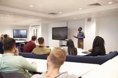 大学生在有男性讲师的一间教室学习 库存照片
