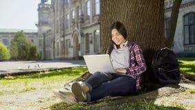 大学生在树下在校园里,使用膝上型计算机,微笑坐她的面孔 免版税库存图片