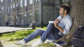 大学生在树下坐校园,解决在笔记本的任务,巧妙 股票录像