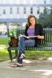大学生在长凳的阅读书 免版税库存照片
