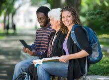 大学生坐栏杆在校园 免版税库存照片