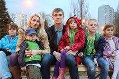 大家庭在晚上坐长凳。 库存图片