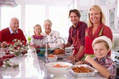 大家庭小组涂抹的圣诞节土耳其在厨房里 免版税库存照片