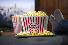 大容器玉米花和放松由电视 免版税库存图片