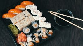 大寿司设置与许多寿司,卷, maki, nigiri, gunkan 时髦的寿司在黑木桌上设置在大豆旁边 影视素材