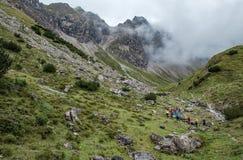 大小组远足者在奥伯斯特多夫附近的allgaeu阿尔卑斯在一多云天 免版税库存照片