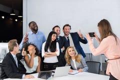大小组商人在一起办公室,拍同事的照片细胞巧妙的电话的,队女实业家 库存图片