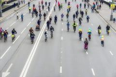 大小组在街道上的自行车骑士,城市马拉松,回到我们,无法认出 体育,健康生活方式概念 为 库存图片