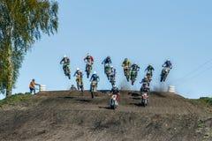 大小组在跳过山的摩托车的车手 免版税图库摄影