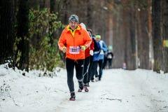 大小组赛跑者运动员在雪森林里跑 免版税库存照片