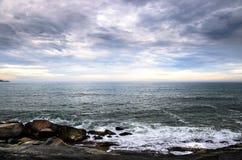 大岩石、许多云彩和天际在海景 免版税图库摄影