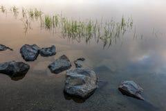 大岩石在寂静的水中 库存照片