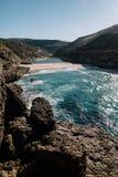 大岩石在海滩和在海洋 库存照片