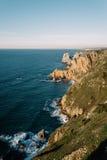 大岩石在海滩和在海洋 库存图片