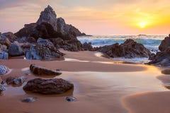 大岩石风景在日落的海洋海滩 库存图片