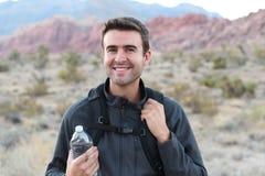 大峡谷旅行-有背包和水瓶的愉快的人山远足者在岩石干燥山 免版税库存照片