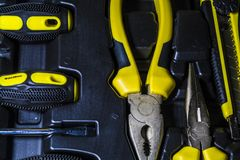 大工具箱房子的黑和黄色颜色箱子的 扁鼻子钳子、螺丝刀、文具刀子和少年 免版税图库摄影