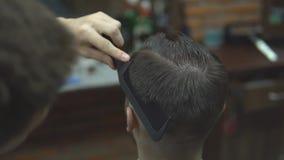 大师剪头发,并且人在理发店,美发师胡子做一个年轻人的发型 股票录像