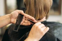 大师剪头发,并且人在理发店,美发师胡子做一个年轻人的发型 库存图片