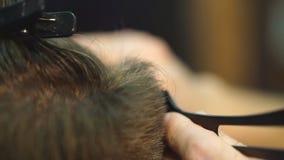 大师剪头发,并且人在理发店,美发师胡子做一个年轻人的发型 股票视频